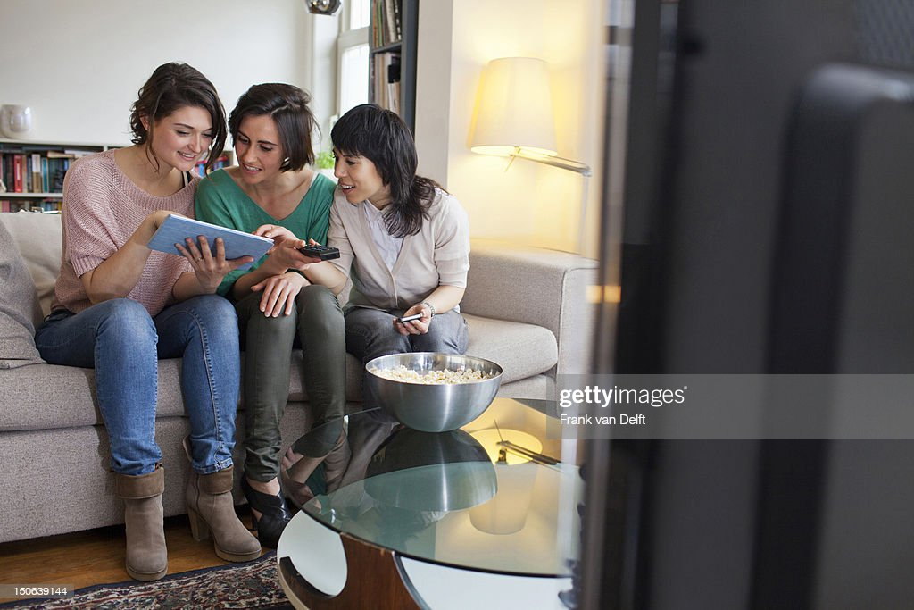 Women using tablet computer on sofa : Stock Photo