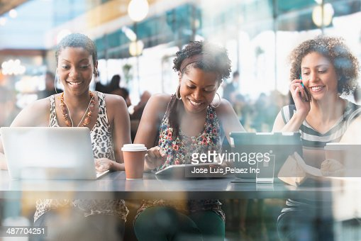 Women using technology in cafe