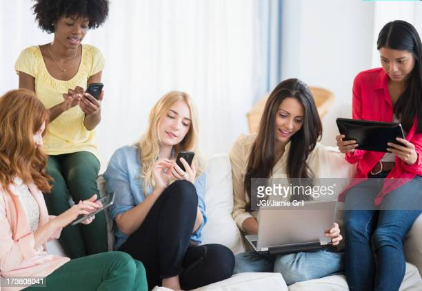 Women using technology on sofa