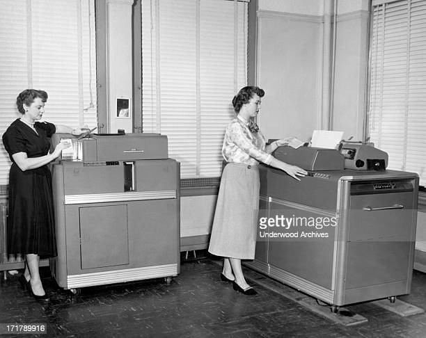 Women using two different IBM punch card machines Cleveland Ohio circa 1954 On the left is a Summary Punch Machine and on the right is the type 407...