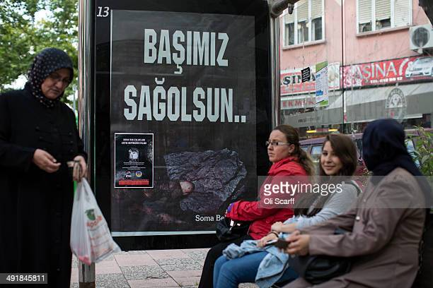 Women wait at a bus stop near a poster bearing the slogan which reads 'My condolences' on May 17 2014 in Soma Turkey Rescuers are still trying to...