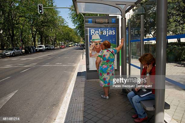 Women wait for a bus as a street thermometer reads 45 degress near the Manzanares river on July 21 2015 in Madrid Spain A third heat wave this summer...