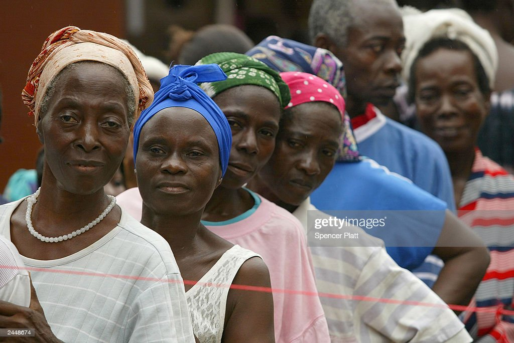 Women wait in a line at a camp for those displaced by war during the distribution of relief items by the aid group Caritas August 30 2003 in Monrovia...