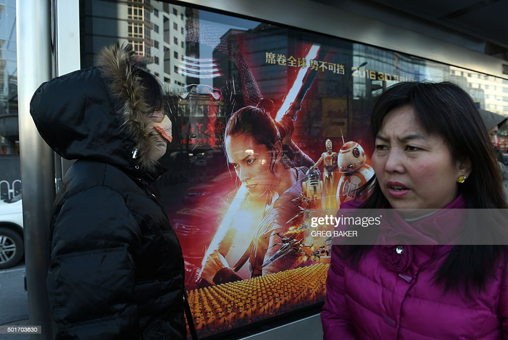 Women wait in front of a poster for 'Star Wars The Force Awakens' at a bus stop in Beijing on December 17 2015 The movie opens in China on January 9...