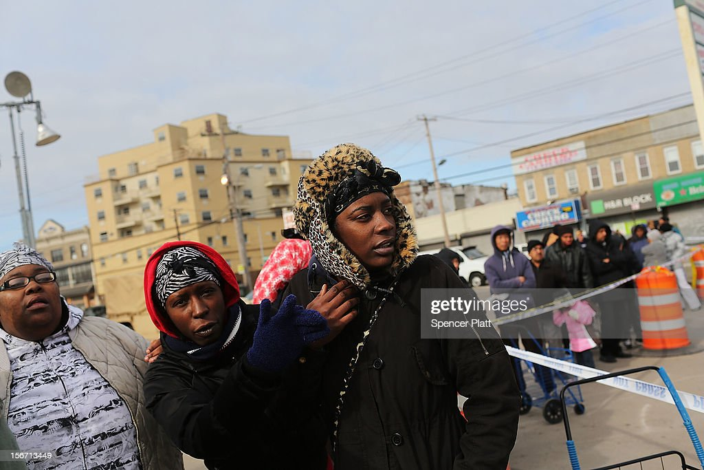 Women wait in line at a food distribution site in the heavily damaged Rockaway neighborhood where a large section of the iconic boardwalk was washed away on November 19, 2012 in the Queens borough of New York City. Three weeks after Superstorm Sandy slammed into parts of New York and New Jersey, thousands are still without power and heat.