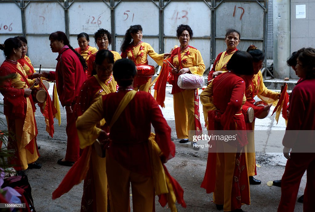 Women wait to perform gong and drum outside a restaurant to celebrate the opening ceremony on November 6, 2012 in Chongqing, China.