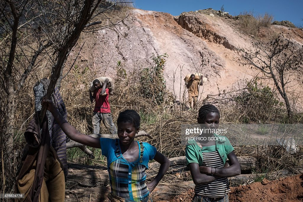 Women wait to receive mine waste material to separete cobalt from mud and rocks in a mine between Lubumbashi and Kolwezi on May 31 2015 AFP...