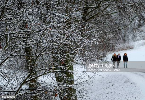 Women walk after snow fall on December 11 2017 in Sundbyberg near Stockholm High winds and heavy snow in Europe on Monday stranded thousands of...