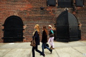 Women walk along a street which was flooded during Hurricane Sandy on October 23 2013 in the Red Hook section of the Brooklyn borough of New York...