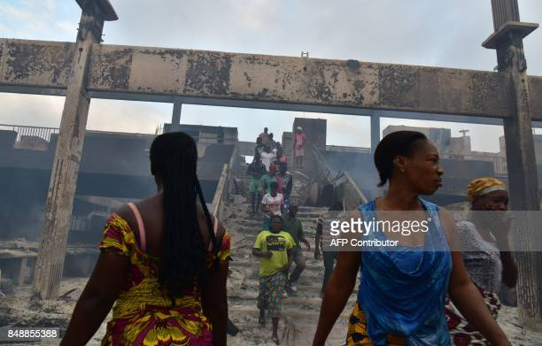 Women walk amid debris in the market after a fire devastated the building during the night on September 18 2017 in Abobo neighborhood of Abidjan /...