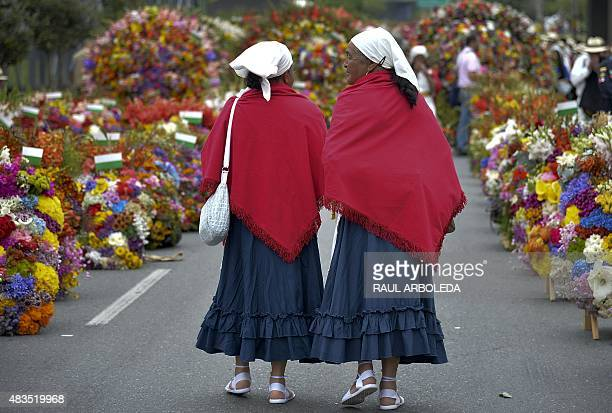 Women walk between lines of flower arrangements during the traditional 'Silleteros' parade held as part of the Flower Festival in Medellin Antioquia...