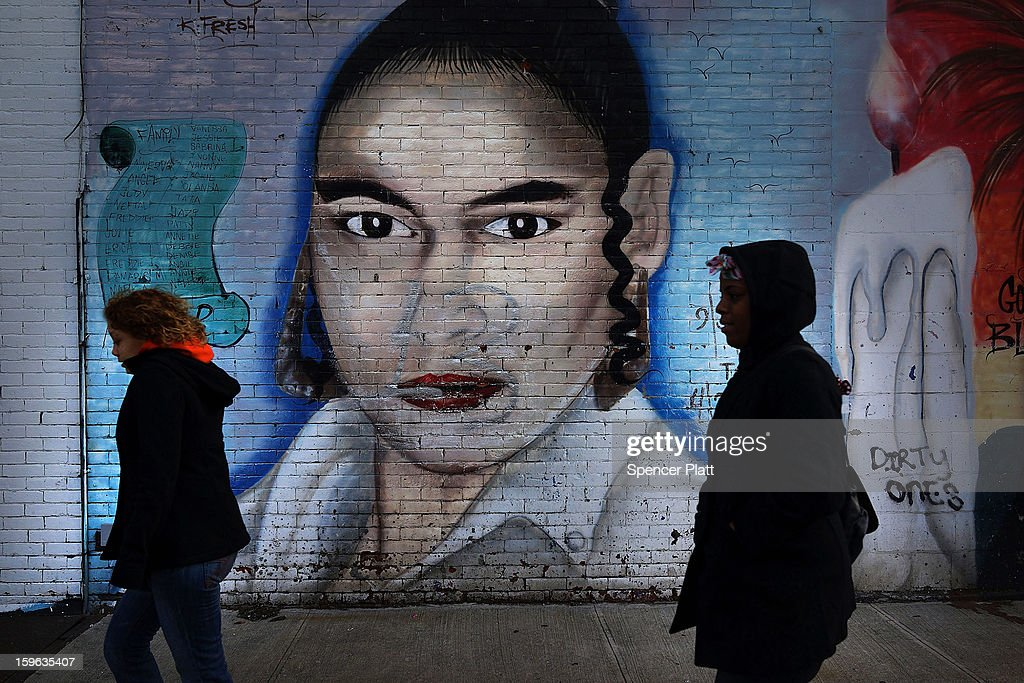 Women walk by a graffiti memorial in memory of a woman in the Bedford-Stuyvesant neighborhood on January 17, 2013 in the Brooklyn borough of New York City. Visual memorials honoring residents who in many cases met violent ends decorate many Brooklyn neighborhoods. New York Governor Andrew Cuomo recently signed into law the New York Secure Ammunition and Firearms Enforcement Act, one of the toughest gun laws in the country.