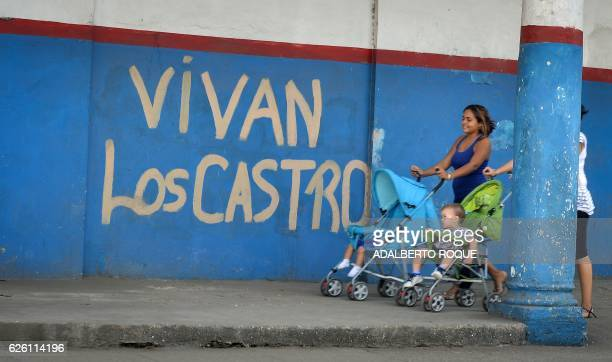 TOPSHOT Women walk by a graffiti reading 'Long Live The Castros' in Havana on November 27 2016 two days after the death of Cuban revolutionary leader...