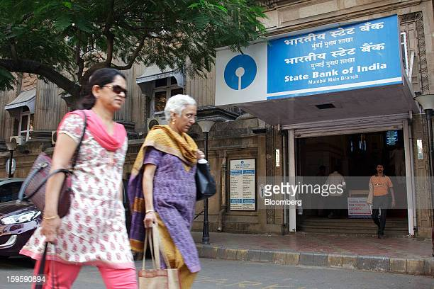 Women walk by a State Bank of India bank branch in Mumbai India on Wednesday Jan 16 2013 India's financial system has been made vulnerable by a...