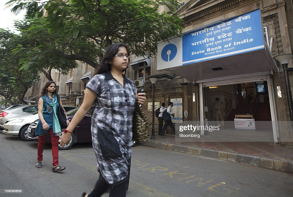 Women walk by a State Bank of India bank branch in Mumbai, India, on Wednesday, Jan. 16, 2013. India's financial system has been made vulnerable by a deterioration in bank assets and a lack of capital as the economy slowed, according to the International Monetary Fund. Photographer: Kuni Takahashi/Bloomberg via Getty Images