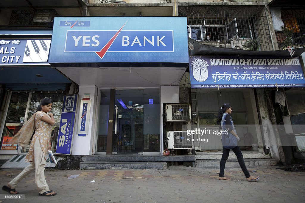 Women walk by a Yes Bank Ltd. automated teller machine (ATM) branch in Mumbai, India, on Wednesday, Jan. 16, 2013. India's financial system has been made vulnerable by a deterioration in bank assets and a lack of capital as the economy slowed, according to the International Monetary Fund. Photographer: Kuni Takahashi/Bloomberg via Getty Images