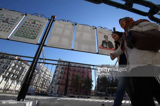 Women walk by electoral campaign posters for the upcoming legislative elections in Algiers centers Algeria on April 12 2017