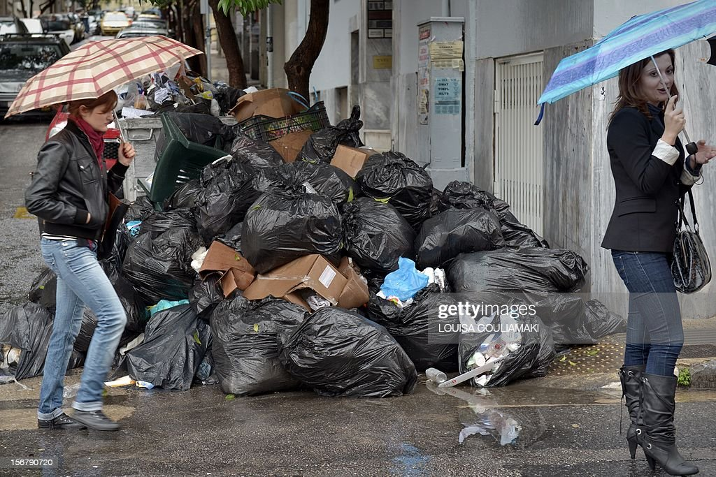 Women walk by piles of garbage in a street of Athens on November 21, 2012 following the walkout of municipal workers protesting public sector layoffs. Greek Prime Minister Antonis Samaras today called on his EU peers to step up efforts to release vital funds to Athens, warning of a threat to the eurozone after finance ministers failed to settle the matter.