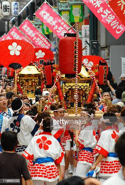 Women walk carrying a portable Shrine at Tenjinbashisuji Shopping Street on July 23 2011 in Osaka Japan The event is to promote the Tenjin Festival...