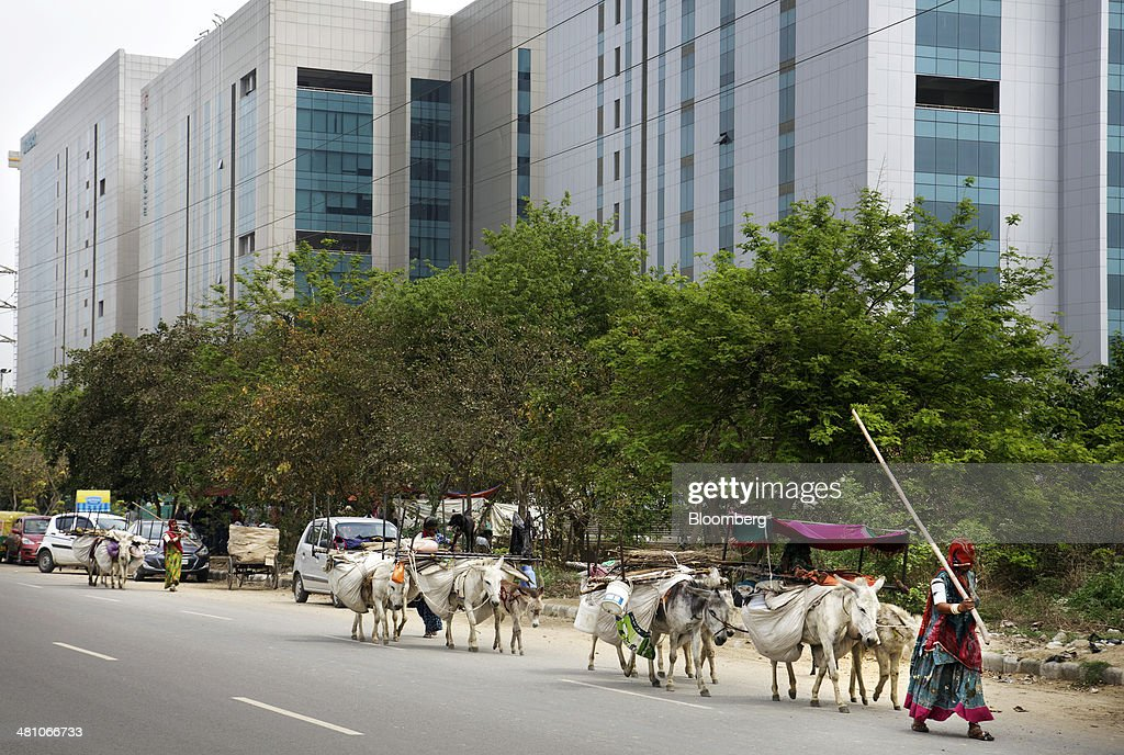 Women walk donkeys transporting goods past commercial buildings in Gurgaon, India, on Wednesday, March 26, 2014. Indian stocks rose, sending the benchmark index to a record, after the rupee rose to an eight-month high and sovereign bonds gained on speculation the worlds largest democracy will elect a government capable of reviving economic growth. Photographer: Kuni Takahashi/Bloomberg via Getty Images