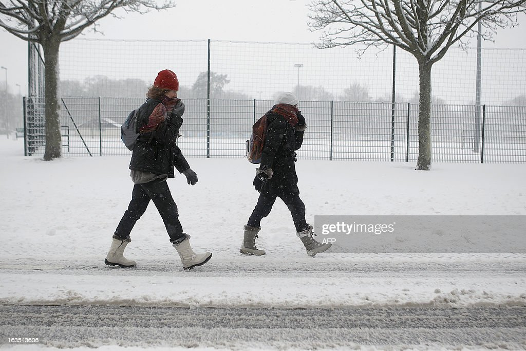 Women walk on a snowy sidewalk, on March 12, 2013 in Caen, northwestern France, during a heavy snow storm on France. Overnight Monday nearly 500 cars were blocked near Cherbourg where snowdrifts piled up 60 centimetres (almost two feet) as winds reached 100 kilometres (more than 60 miles) an hour. Twenty-six regions in northwest and northern France were put on orange alert because of heavy snowfalls, which Meteo France said were 'remarkable for the season because of the expected quantity and length of time'.