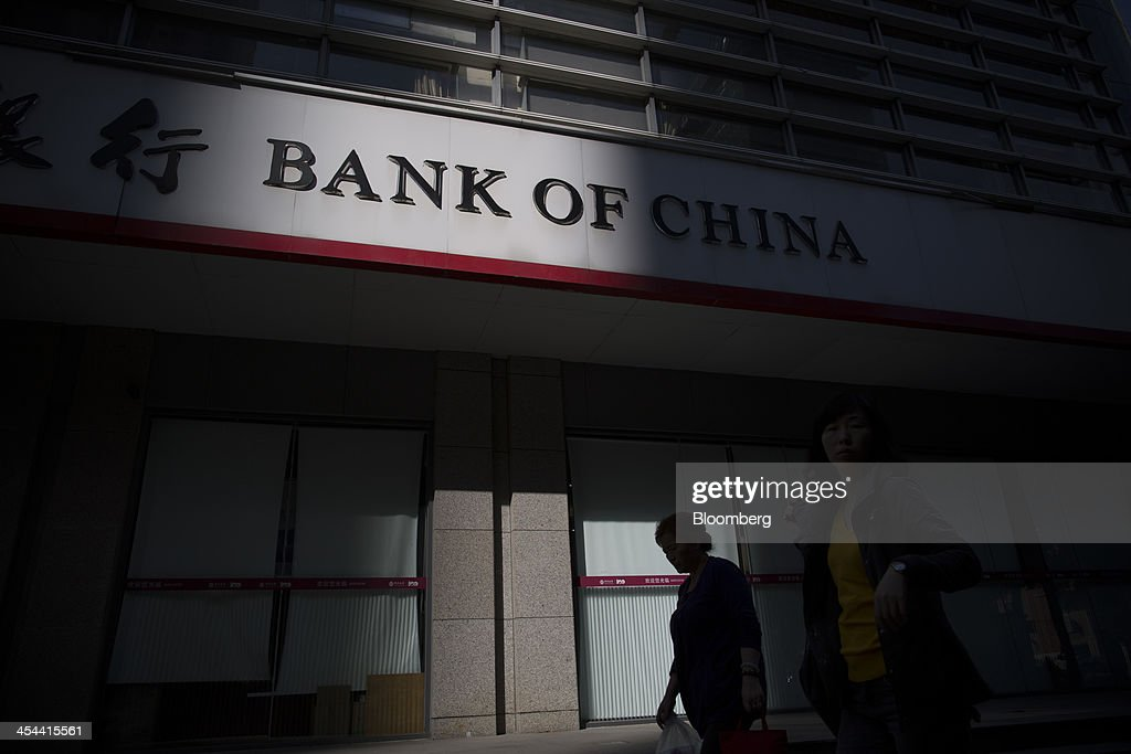 Women walk past a branch of Bank of China Ltd. in the Tianhe district of Guangzhou, Guangdong province, China, on Monday, Nov. 25, 2013. China is proposing the largest package of economic reforms since the 1990s to stoke growth in the worlds biggest emerging market. Photographer: Brent Lewin/Bloomberg via Getty Images