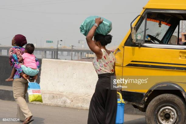 Women walk past a broken down yellow bus at Apongbon area of Lagos Nigeria on Tuesday February 7 2017 Lagos State Government has announced its...