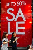 Women walk past a commercial sign advertising a sale at a shopping district in Seoul on July 26 2016 South Korea's economy posted improved growth in...