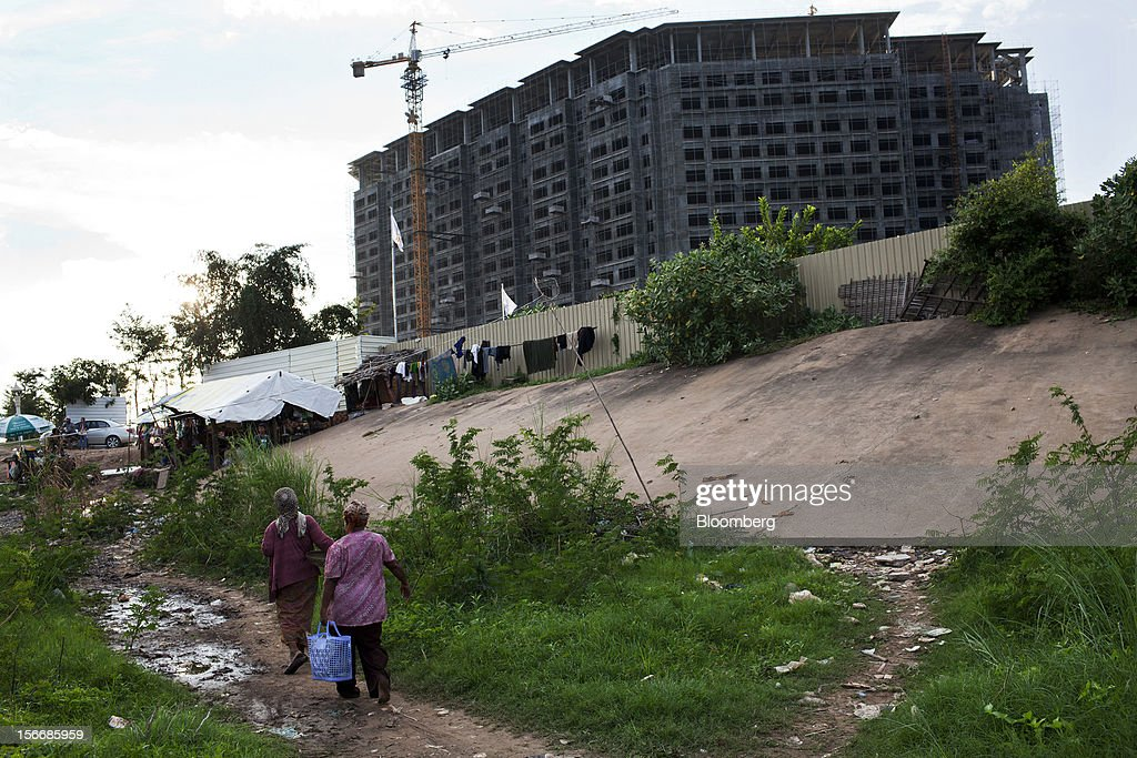 Women walk past a development site by Sokha Hotels & Resorts, a unit of Sokimex Group, under construction on the Chroy Changvar peninsula in Phnom Penh, Cambodia, on Saturday, Nov. 17, 2012. U.S. President Barack Obama arrives in Phnom Penh later today to join the Association of Southeast Asian Nations (Asean) East Asia Summit, which also includes leaders from Japan, South Korea, India, Russia, Australia and New Zealand. Photographer: Will Baxter/Bloomberg via Getty Images