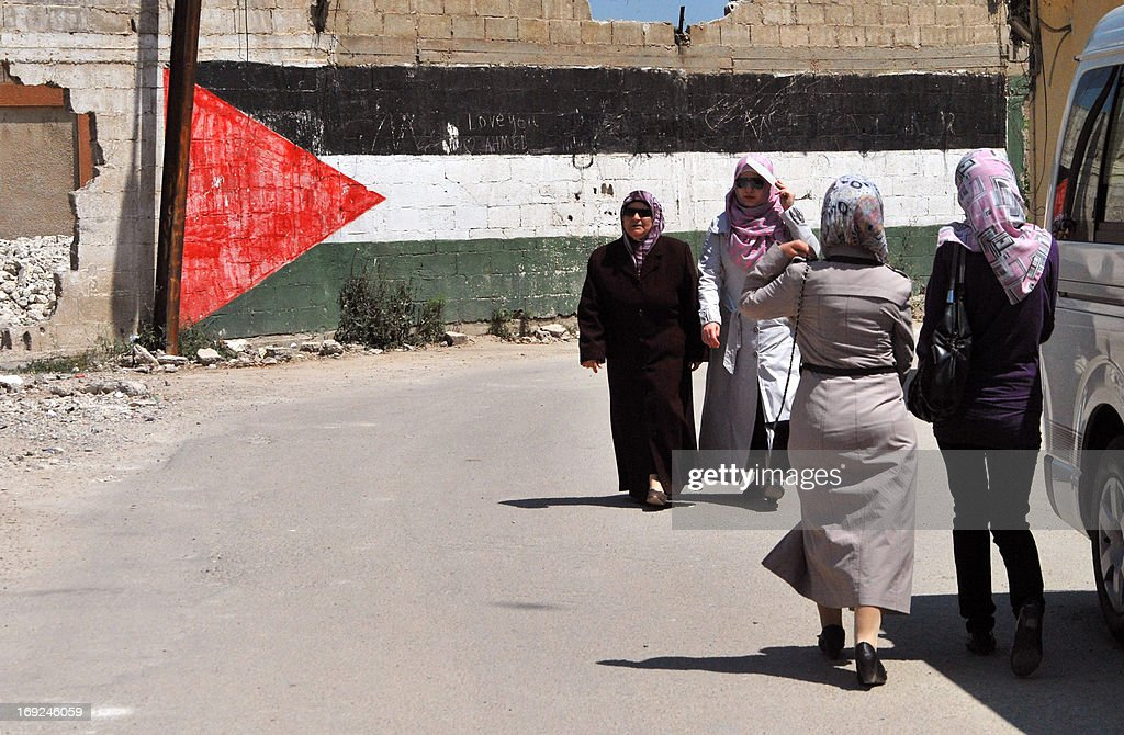 Women walk past a giant Palestinian flag painted on a wall at a camp for Palestinian refugees on May 22, 2013 in Homs, Syria. The conflict in Syria has displaced more than two-thirds of Palestinian refugees living in the country, the UN Relief and Works Agency for Palestine refugees said.