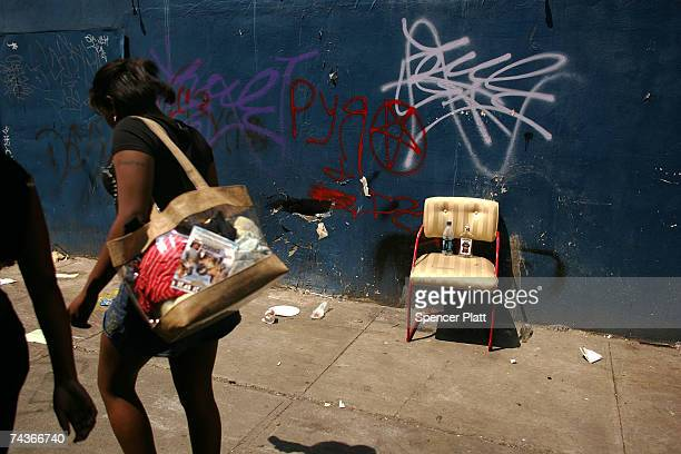 Women walk past a grafitti strewn wall a May 31 2007 at Coney Island in Brooklyn New York Coney Island has been a summer destination for millions of...