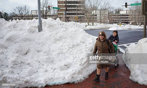Women walk past a large mound of snow in Chevy Chase Maryland on January 26 2016 The US capital remained crippled Tuesday by the messy aftermath of...