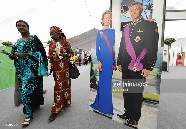 Women walk past a life size cutout of King Philippe and Queen Mathilde of Belgium as they visit the 'Village de la Francophonie' on November 25 2014...