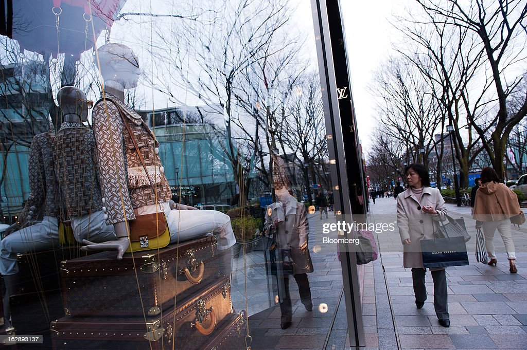 Women walk past a Louis Vuitton store, operated by LVMH Moet Hennessy Louis Vuitton SA, in the shopping district of Omotesando in Tokyo, Japan, on Friday, March 1, 2013. Japan's consumer prices fell for the eighth time in nine months, highlighting the challenges facing the Bank of Japan in reaching a 2 percent inflation target. Photographer: Noriko Hayashi/Bloomberg via Getty Images
