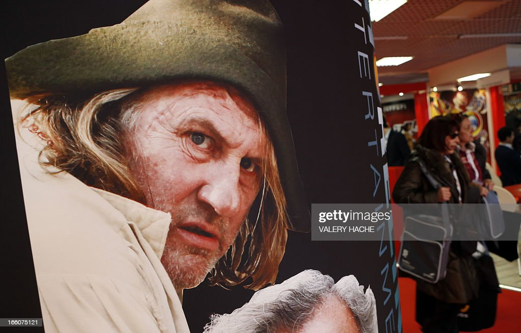 Women walk past a movie poster bearing the face of French actor Gerard Depardieu as they visit the MIPTV, one of the world's largest broadcasting and audio-visual trade show, on April 8, 2013 in Cannes, southeastern France.