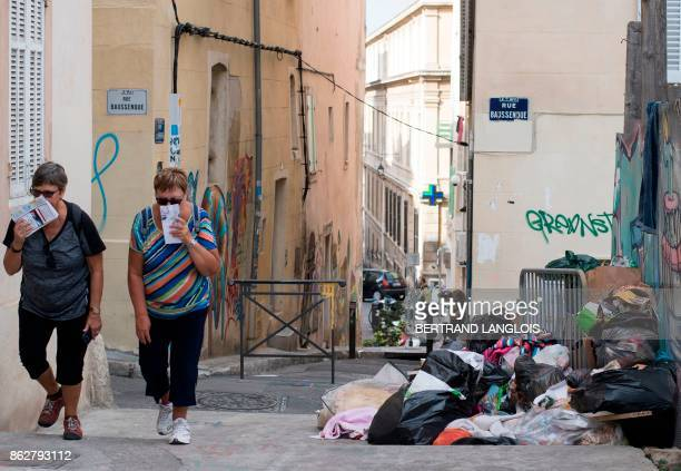 Women walk past a pile of uncollected trash during a strike by refuse collectors on October 18 in the Panier district of Marseille southern France /...