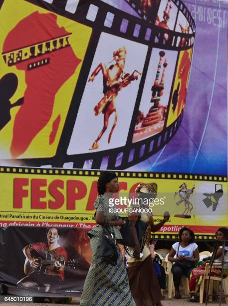 Women walk past a poster for the PanAfrican Film and Television Festival in Ouagadougou on February 24 on the eve of the opening of the festival Held...