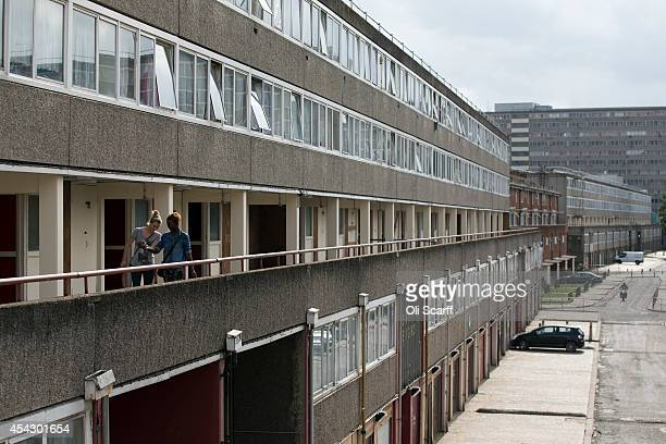 Women walk past a residential tower block in an area of Southwark with a high concentration of social housing on August 28 2014 in London England A...