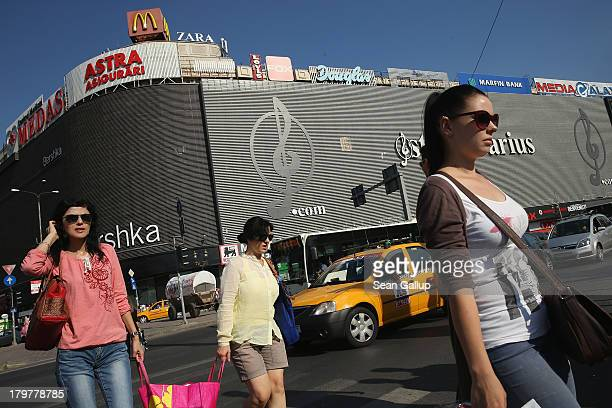 Women walk past a shopping mall in the city center on September 6 2013 in Bucharest Romania While the country's economic output has risen...