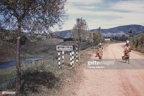 Women walk past a sign showing the Equator line in Uganda circa 1960