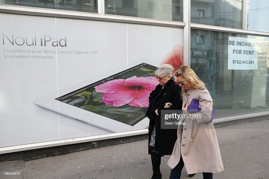 Women walk past an advertisement for the Apple iPad and a shop space up for rent on March 7, 2013 in Bucharest, Romania. Both Romania and Bulgaria have been members of the European Union since 2007 and restrictions on their citizens' right to work within the EU are scheduled to end by the conclusion of this year. However, Germany's interior minister announced recently that he would veto the two countries' entry into the Schengen Agreement, which would not affect labour rights but would prevent passport-free travel.