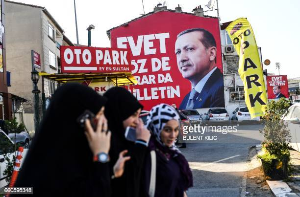 Women walk past an 'EVET' campaign billboard showing the portrait of Turkish President Recep Tayyip Erdogan on March 29 2017 in Istanbul two weeks...