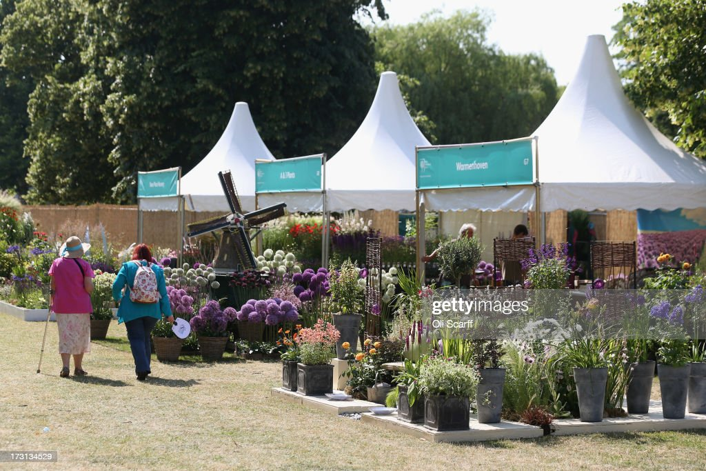 Women walk past exhibitors stands at the Hampton Court Palace Flower Show on July 8, 2013 in London, England. Hampton Court Palace Flower Show opens to the public tomorrow and runs until July 14, 2013. It is the world's largest flower show with over 600 exhibitors spread over 34 acres.