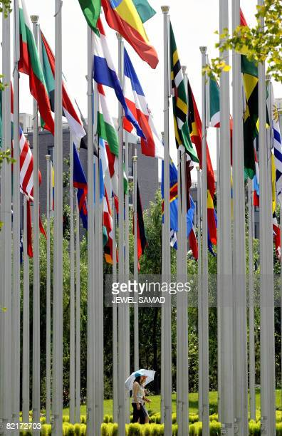 Women walk past poles displaying national flags of some of the participating Olympic countries at the Olympic Village in Beijing on August 2 2008 The...