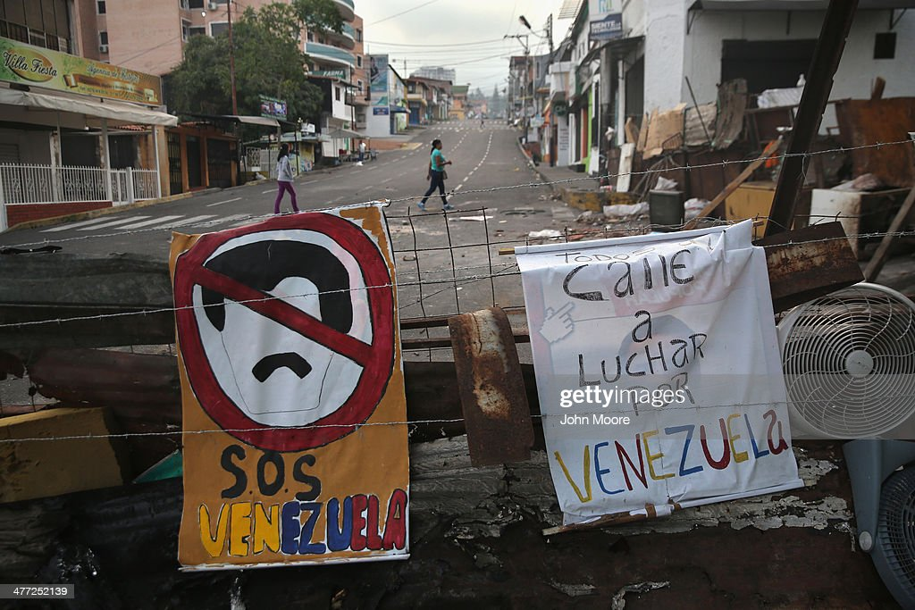 Women walk past protesters' barricades on March 8, 2014 in San Cristobal, the capital of Tachira state, Venezuela. Shortage of such products as flour, milk and sugar have made life increasingly difficult for residents of Tachira, which has been a focal point for anti-government protests for almost a month.
