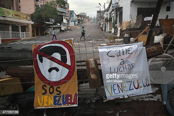 Women walk past protesters' barricades on March 8 2014 in San Cristobal the capital of Tachira state Venezuela Shortage of such products as flour...