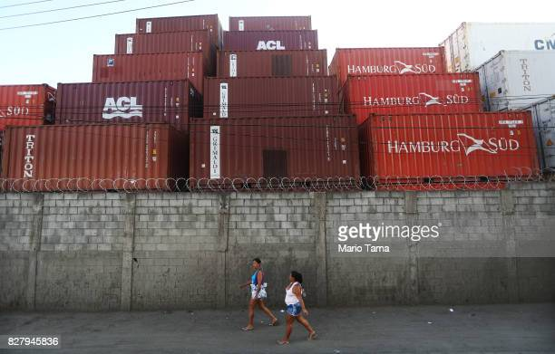 Women walk past shipping containers in the Caju neighbourhood which houses two forlorn shipyards along Guanabara Bay on August 8 2017 in Rio de...