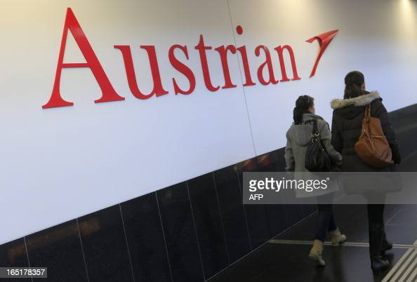 Women walk past the logo of Austrian airlines at the Vienna Schwechat international airport in Schwechat some 20km south east of Vienna on April 1...