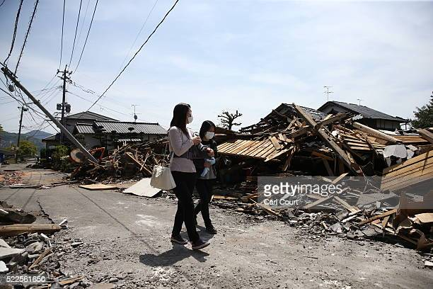 Women walk past the rubble of collapsed houses following an earthquake on April 20 2016 in Mashiki near Kumamoto Japan As of April 20 48 people were...