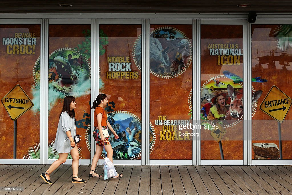 Women walk past Wild Life Sydney wildlife park in the Darling Harbour precinct in Sydney, Australia, on Monday, Dec. 24, 2012. At least 150,000 people from mainland China and across Asia are projected to descend on Sydney, Australia's most populous city, during the New Year's Eve and Chinese New Year period. Photographer: Brendon Thorne/Bloomberg via Getty Images